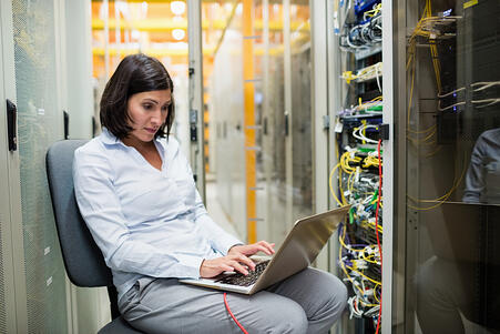 Attentive technician working on laptop in server room